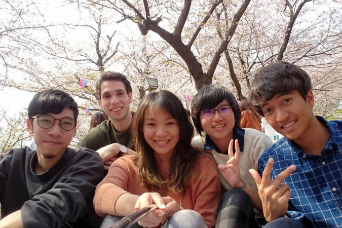 Alumna CHAU Wing-In (second right) gets along well with her friends and colleagues in Japan.  They engaged in the Japanese practice of Hanami – having a picnic and enjoying the cherry blossoms.