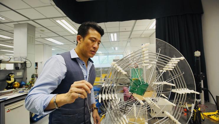 Prof. Patrick Yue demonstrates a wirelessly powered visible light communication (WP VLC) system designed by his graduate students.