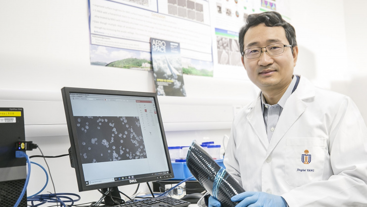 Prof. Yang Jinglei uses carbon fiber reinforced polymer composite (in his hands) and versatile microcapsules (shown on display) to manufacture self-healing, fire-resistant, and impact-proof multifunctional structures, contributing to a lightweight and safer solution for aircraft and electric vehicles.